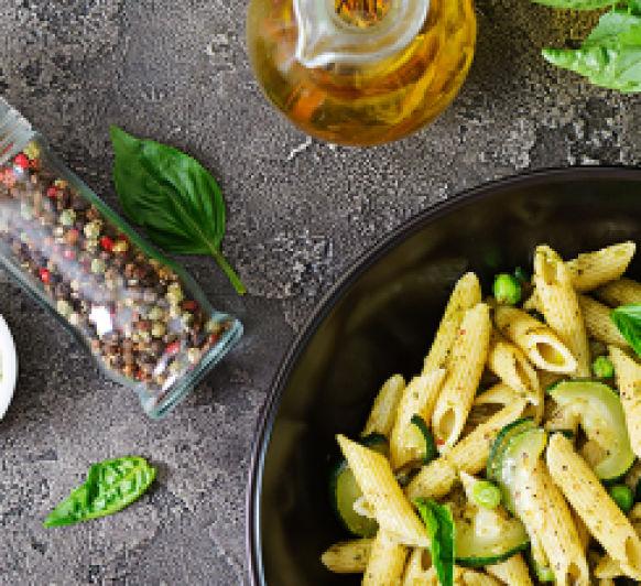 Penne pasta con salsa de pesto, calabacín, guisantes y albahaca
